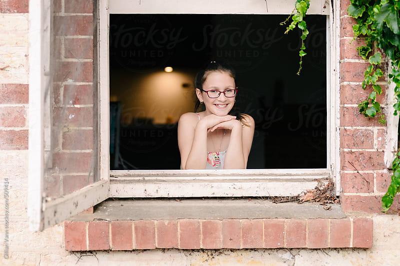 portrait of a teen girl in a window by Gillian Vann for Stocksy United