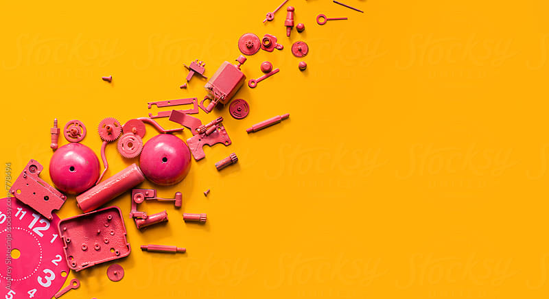 Disassembled pink clock on orange background. by Audrey Shtecinjo for Stocksy United
