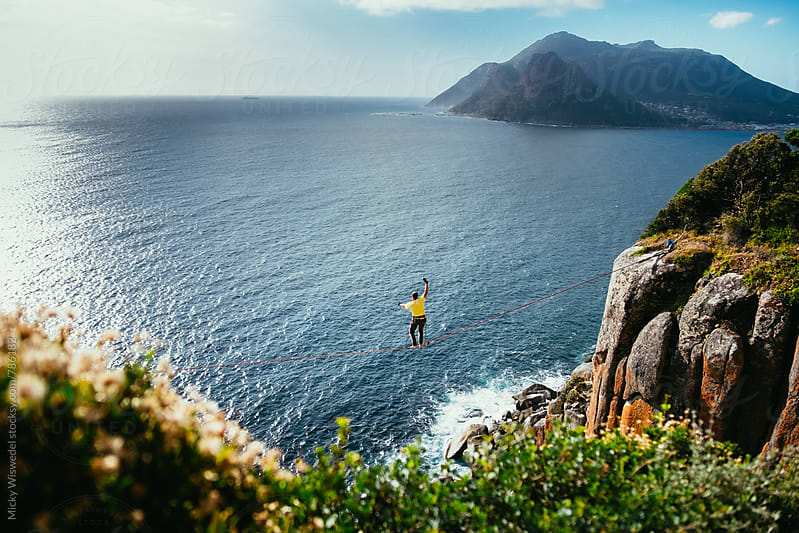 Man tightrope walking a highline between to cliffs above the ocean by Micky Wiswedel for Stocksy United