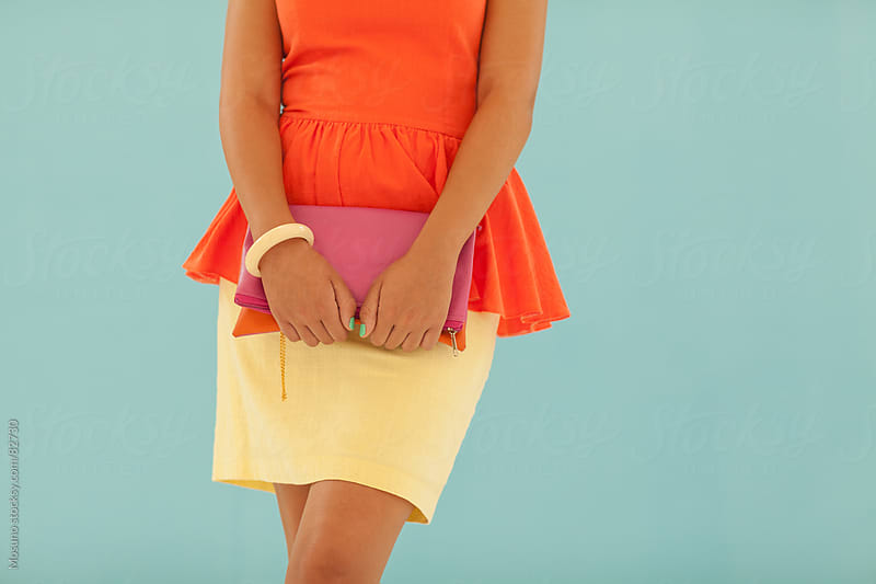 Woman in an orange shirt and yellow skirt standing against blue wall. by Mosuno for Stocksy United