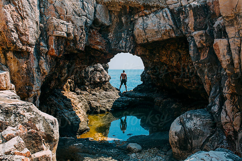 Reflection of a man in a cave by Maja Topcagic for Stocksy United