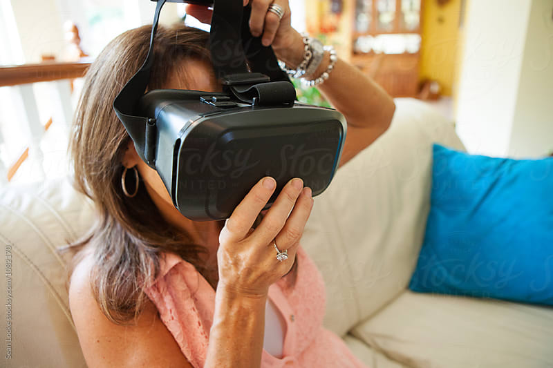 VR: Mature Woman Putting Headset On by Sean Locke for Stocksy United