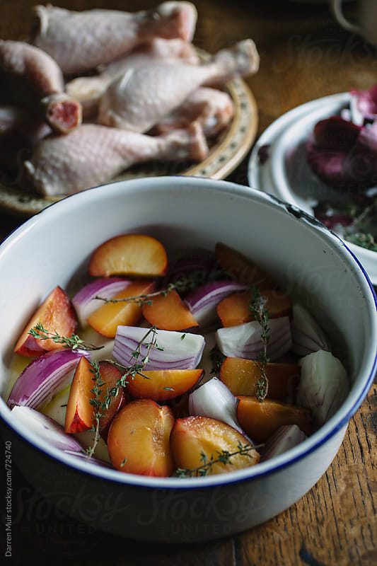 Plums red onions and thyme in a pot with olive oil. by Darren Muir for Stocksy United