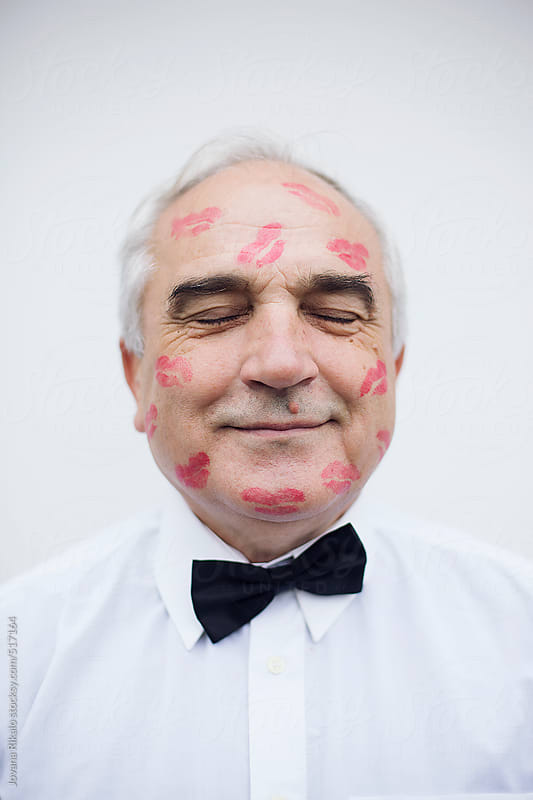 Portrait of an old man with red lip print on his face by Jovana Rikalo for Stocksy United