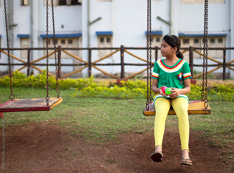 A girl sits on a swing in a park alone  by PARTHA PAL for Stocksy United