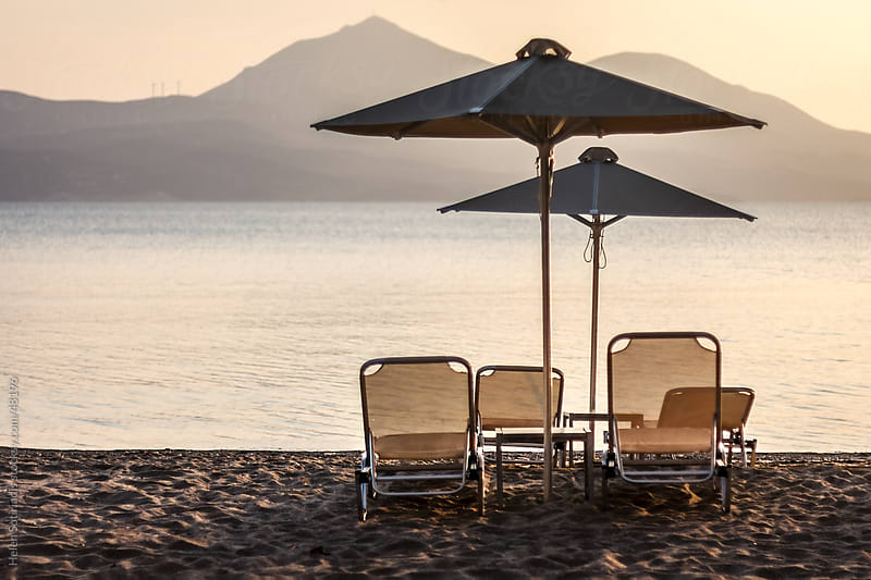 Lounge chairs and umbrellas on the beach by Helen Sotiriadis for Stocksy United