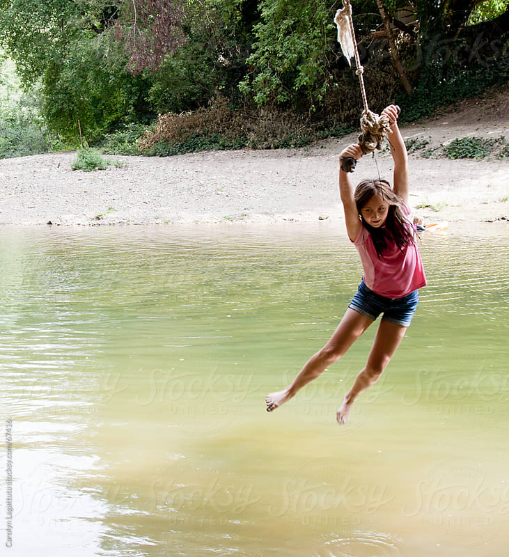 Girl riding a rope swing at the swimming hole by Carolyn Lagattuta for Stocksy United