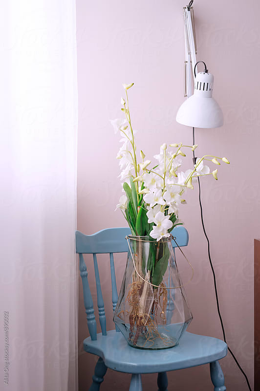 Beautiful bouquet of orchids on a blue chair by Alita Ong for Stocksy United