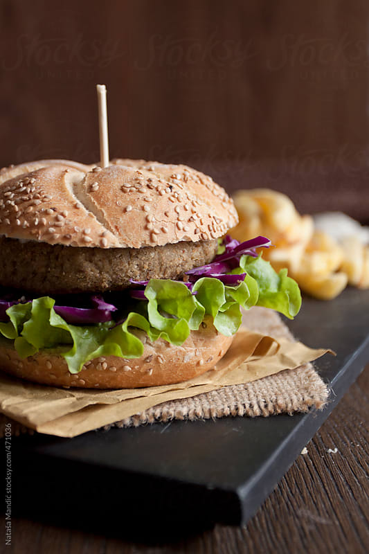 Homemade vegan lentil burger with french fries by Nataša Mandić for Stocksy United