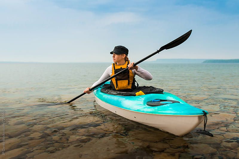 Woman Enjoying Tranquil Sea Kayak Paddle on Clear Freshwater Lake at Summer Family Cottage by JP Danko for Stocksy United