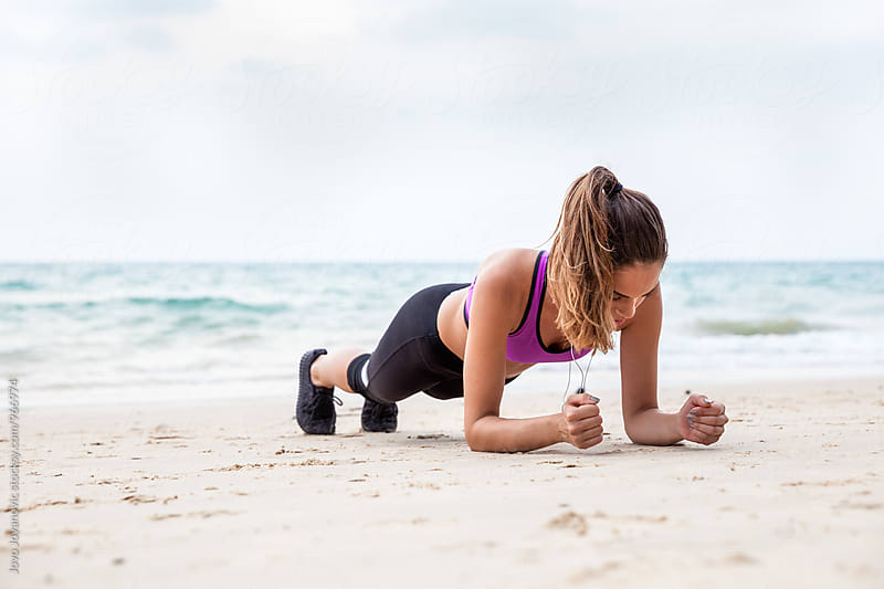 Young woman doing planks at the beach - outdoor fitness  by Jovo Jovanovic for Stocksy United