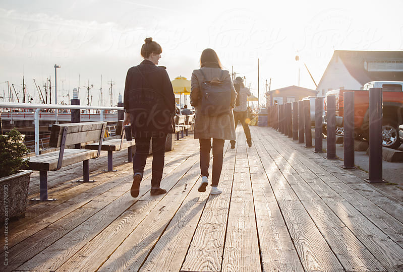 Portrait of two friends walking on boardwalk by Carey Shaw for Stocksy United