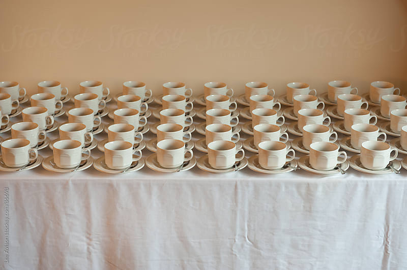 many cups and saucers arranged uniformly  by Lee Avison for Stocksy United