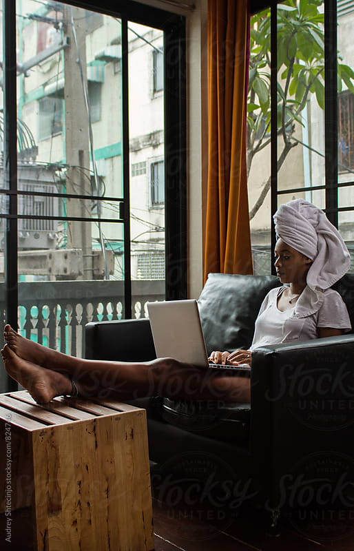 Relaxed young afro-american female using her laptop at her living room. by Audrey Shtecinjo for Stocksy United