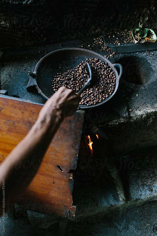 person roasting coffee beans over fire by Cameron Zegers for Stocksy United