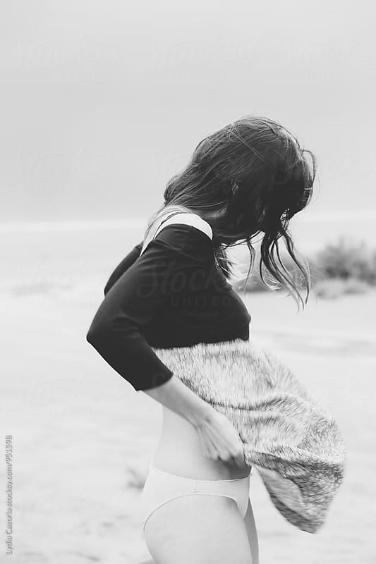 Girl stripping for the wind on the beach by Lydia Cazorla for Stocksy United
