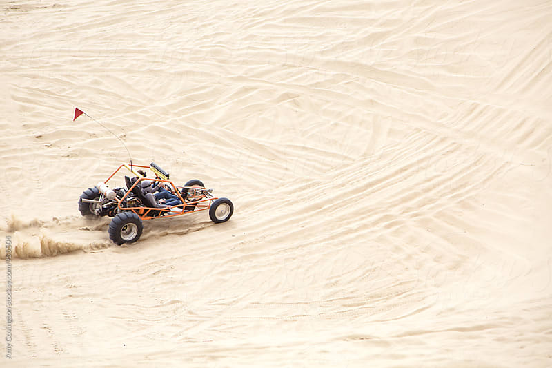 Friends driving a sand rail  by Amy Covington for Stocksy United