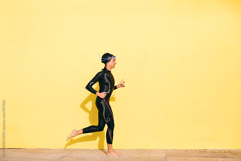Side view of a woman wearing a wetsuit training in front of a yellow wall. by BONNINSTUDIO for Stocksy United