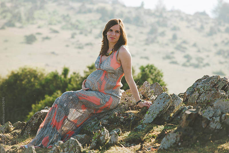 Pregnant woman sitting on a rock on field landscape. by BONNINSTUDIO for Stocksy United