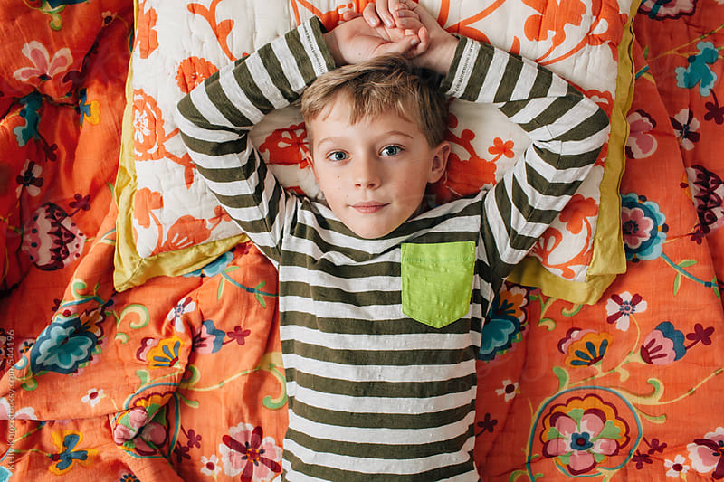 child resting on a bed by Kelly Knox for Stocksy United
