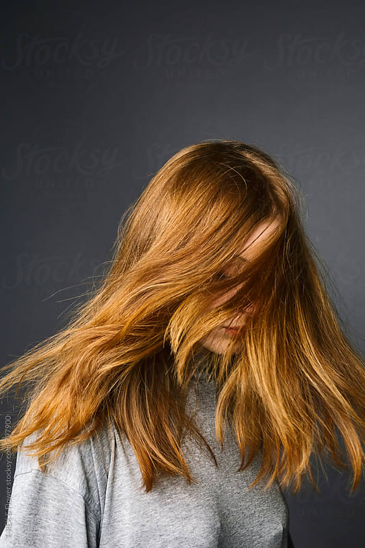 Photo of redheaded woman, face covered with her hair by Danil Nevsky for Stocksy United