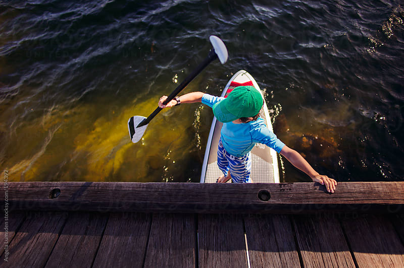 Boy riding a stand up paddle board on a river by Angela Lumsden for Stocksy United