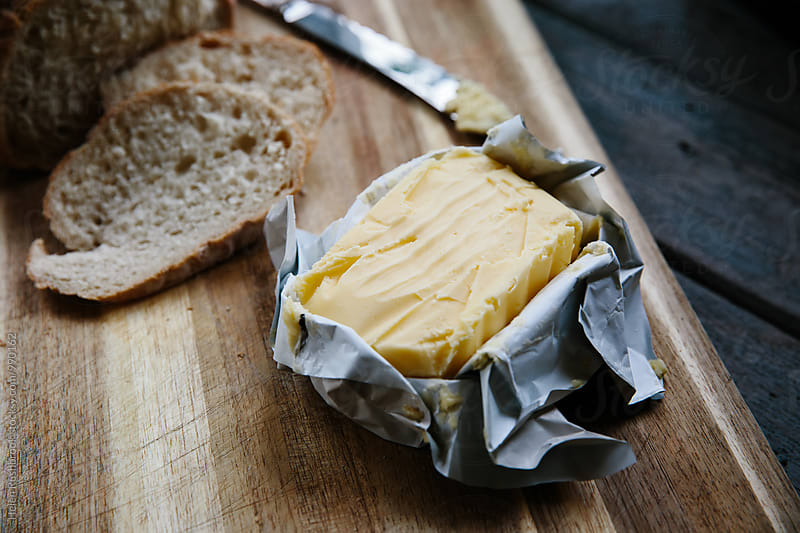 Grass-fed butter and fresh bread by Helen Rushbrook for Stocksy United