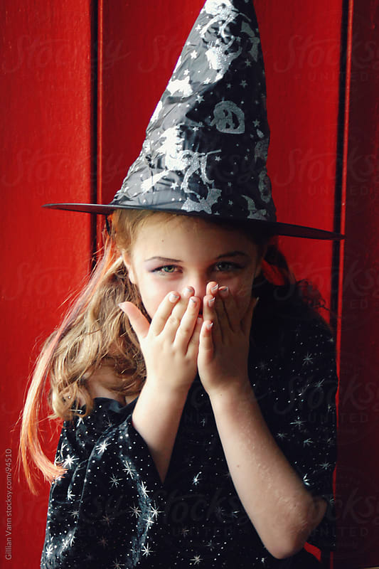 little witch for halloween, overcome by the giggles by Gillian Vann for Stocksy United