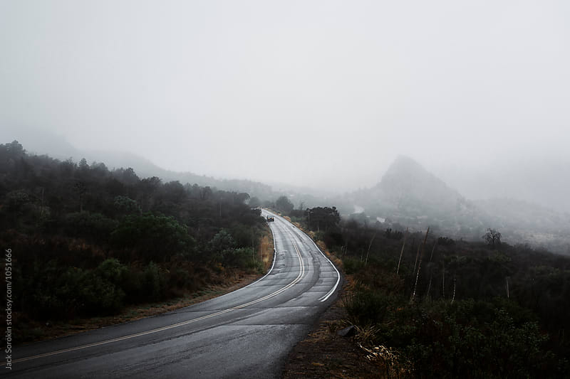 Car Driving Down Foggy Mountain Road by Jack Sorokin for Stocksy United