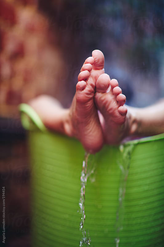 Wrinkled prune appearance of a boy's feet after too long in water by Angela Lumsden for Stocksy United