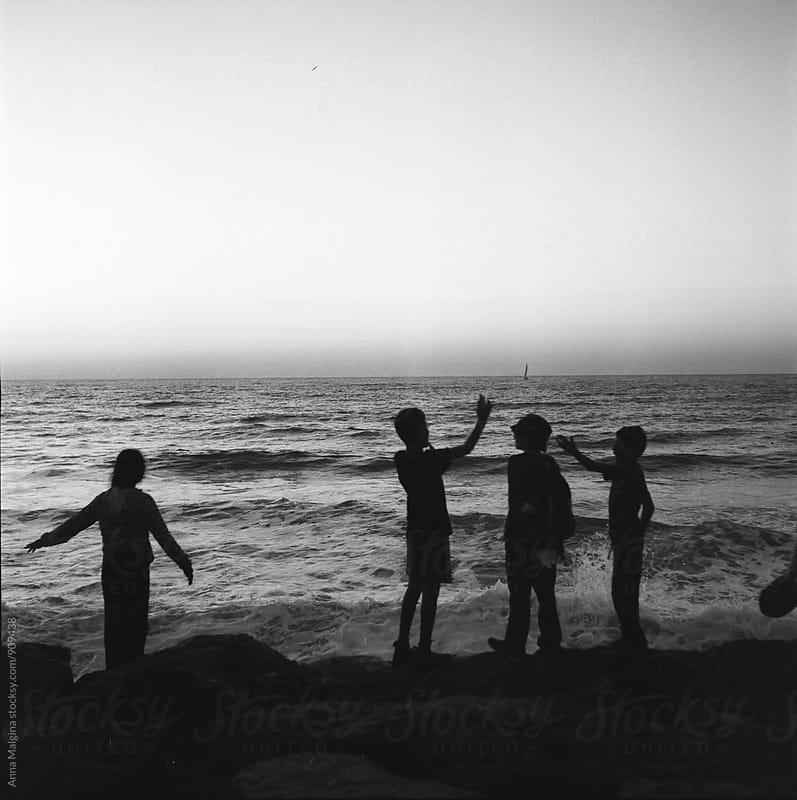 A black and white film photo of boys standing in front of sea by Anna Malgina for Stocksy United