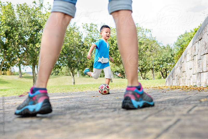 Little kid and mother playing football in park by Lawren Lu for Stocksy United