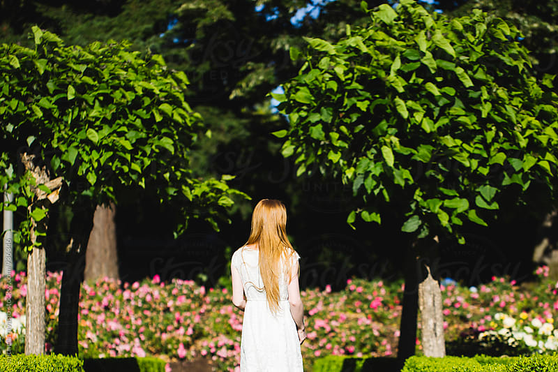 Young woman walking in a flower garden, back view by michela ravasio for Stocksy United