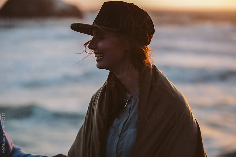 Smiling woman walks along the San Francisco coast by HOWL for Stocksy United
