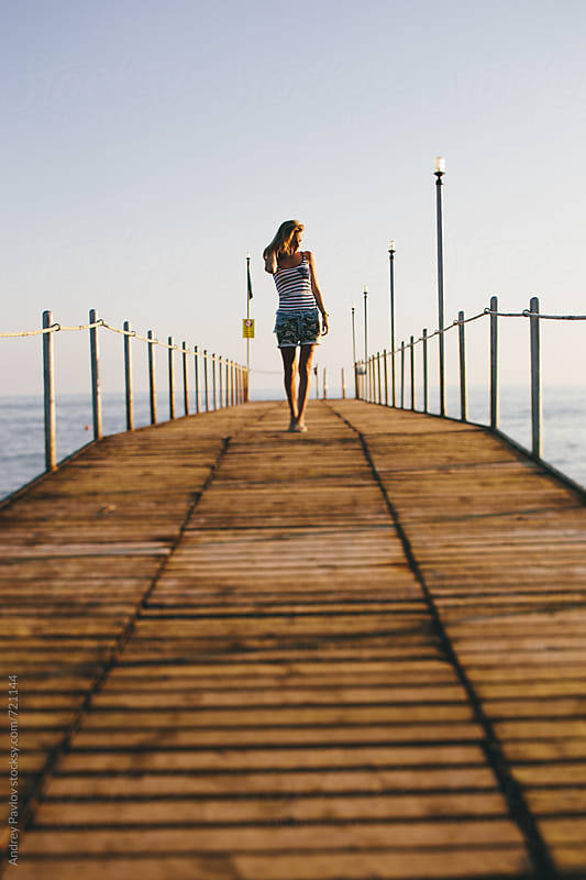 Woman walking on a pier by Andrey Pavlov for Stocksy United