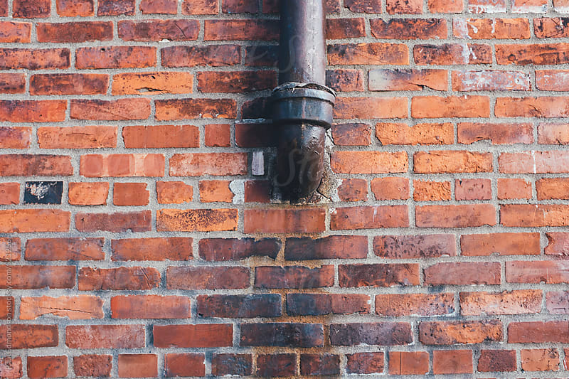 Drain pipe outside of old brick building, close up by Paul Edmondson for Stocksy United