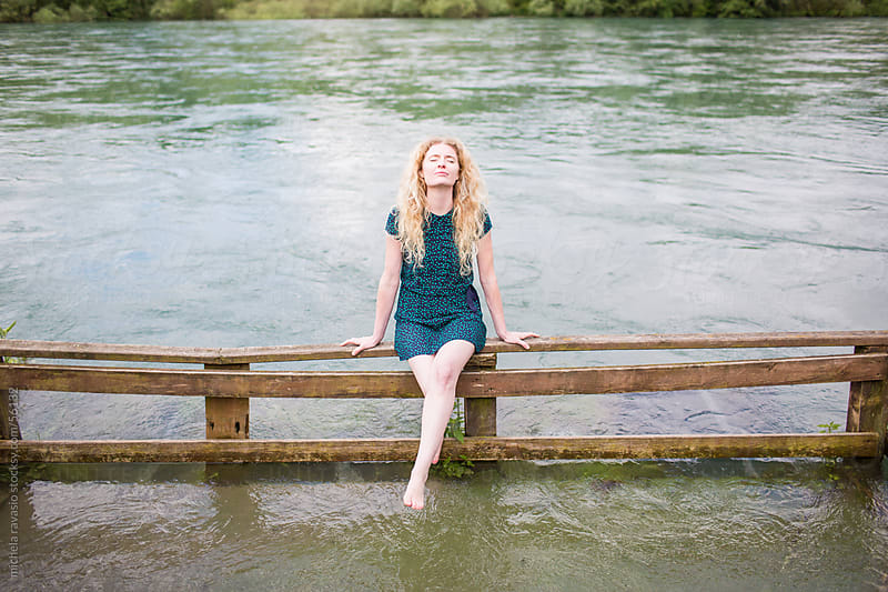 Young woman enjoying the sun along the river by michela ravasio for Stocksy United
