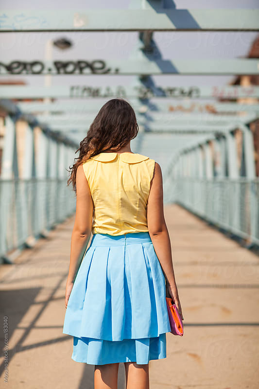 Woman in a blue skirt standing on a gangway.  by Mosuno for Stocksy United