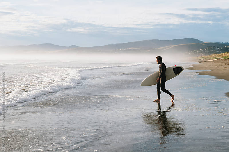Surfing walking into the ocean with surfboard in early morning light, New Zealand. by Thomas Pickard for Stocksy United