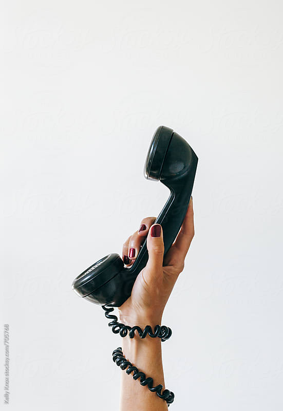 hand holding a vintage black telephone by Kelly Knox for Stocksy United