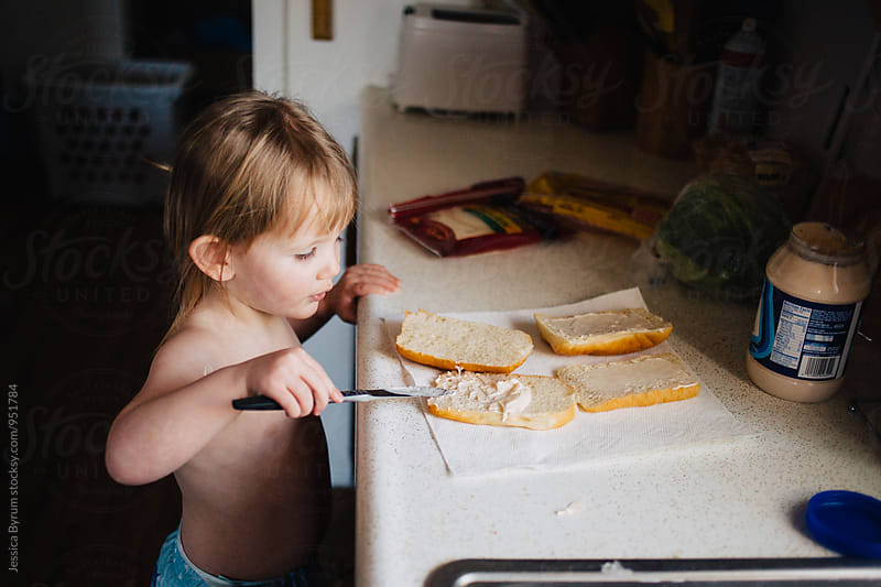 Toddler girl making a sandwich by Jessica Byrum for Stocksy United