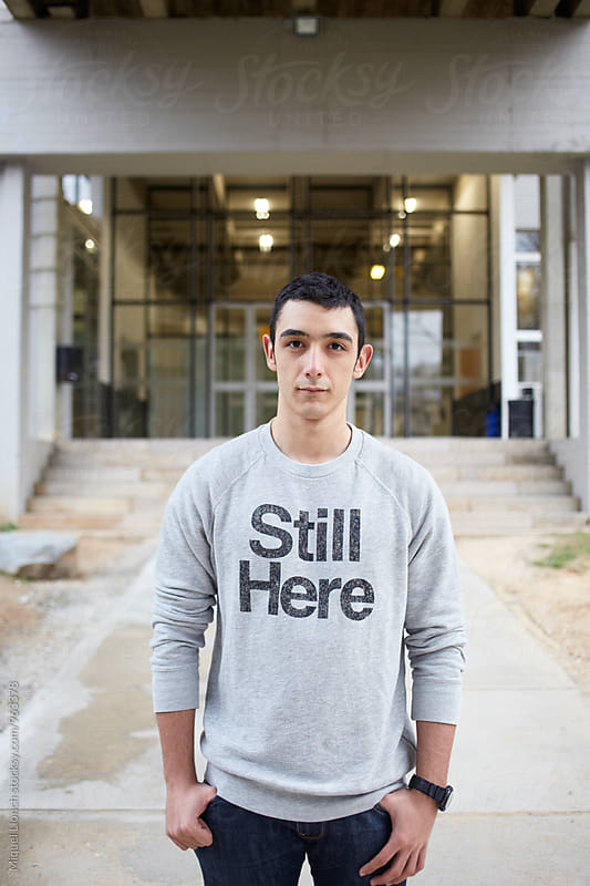 Portrait of  young man with a written sweater of still here by Miquel Llonch for Stocksy United