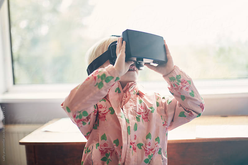 Child using a virtual reality headset by sally anscombe for Stocksy United