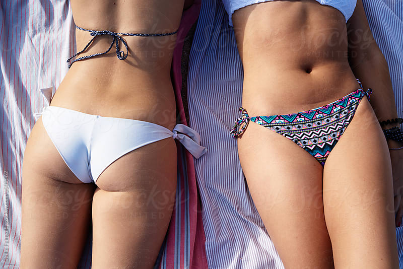 Two unrecognizable girls in bikini on beach blanket  by Guille Faingold for Stocksy United