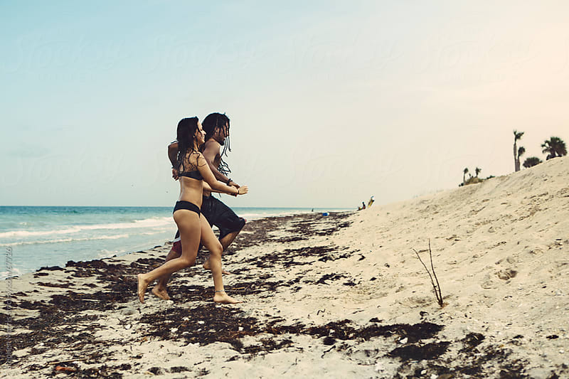 Playful Couple Running on the Beach by Stephen Morris for Stocksy United