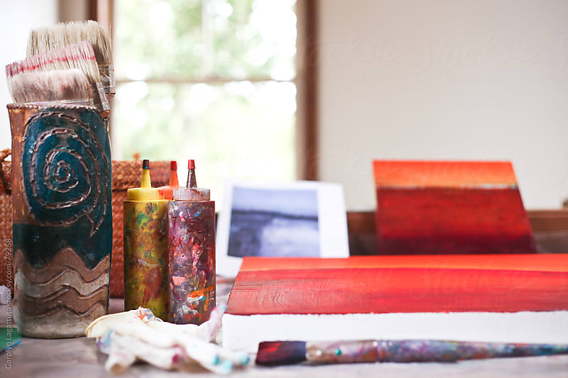 Bottles of paint, a canvas and brushes in an art studio by Carolyn Lagattuta for Stocksy United