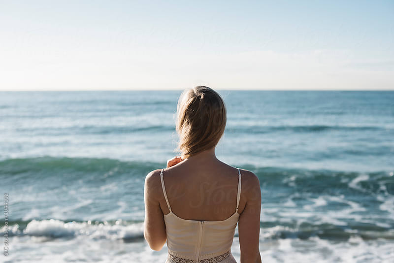 Young woman standing in front of ocean by Simone Becchetti for Stocksy United