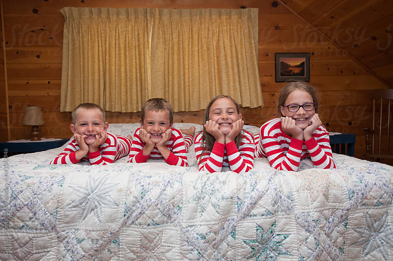Four siblings in matching pajamas lined up on a king bed by Carleton Photography for Stocksy United