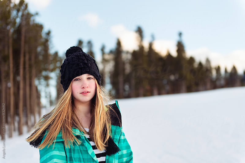 Teenage girl with swinging blonde hair outside in snow in winter by Angela Lumsden for Stocksy United