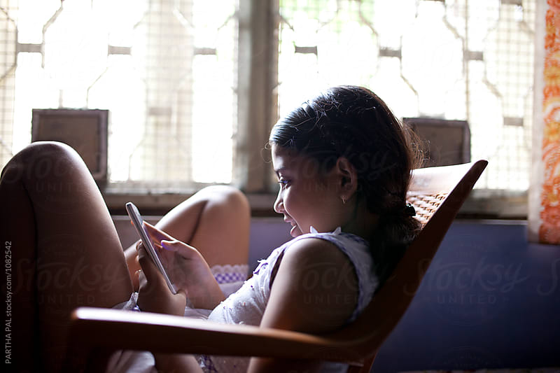 Teenage girl with smartphone inside house by PARTHA PAL for Stocksy United
